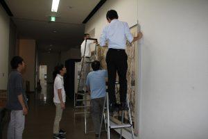 航空写真を展示する学芸員たち