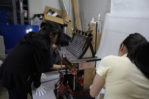 ひな人形の各部の大きさを測る実習生たち