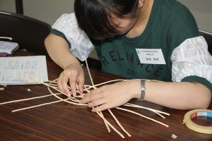紙ひもを編んで蛇籠の模型を作る実習生