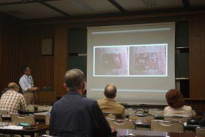 銅鐸に描かれた弓矢とそれを説明する栗山学芸員