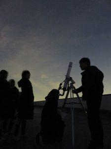 望遠鏡で星を見る中高生