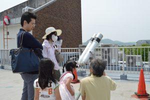 双眼鏡で昼の星を観察する参加者