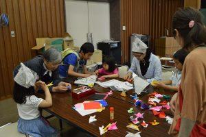 折り紙でかぶと飾りを折る子どもたち