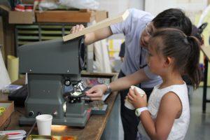偏光顕微鏡で鉱物剥片を観察する参加者