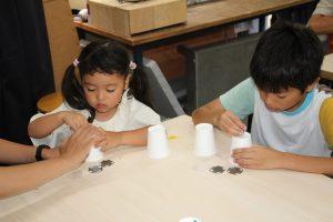 画鋲で紙コップの底に穴をあけている子どもたち