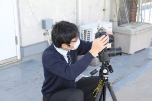 カメラを空に向ける藤井学芸員