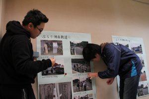 壁にポスターを貼る高校生