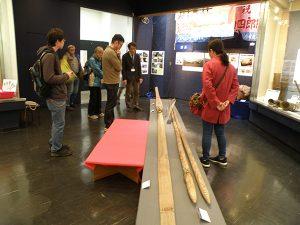 木製の櫓を前に解説をする学芸員と参加者